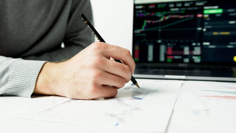 computer screen with graph and man writing