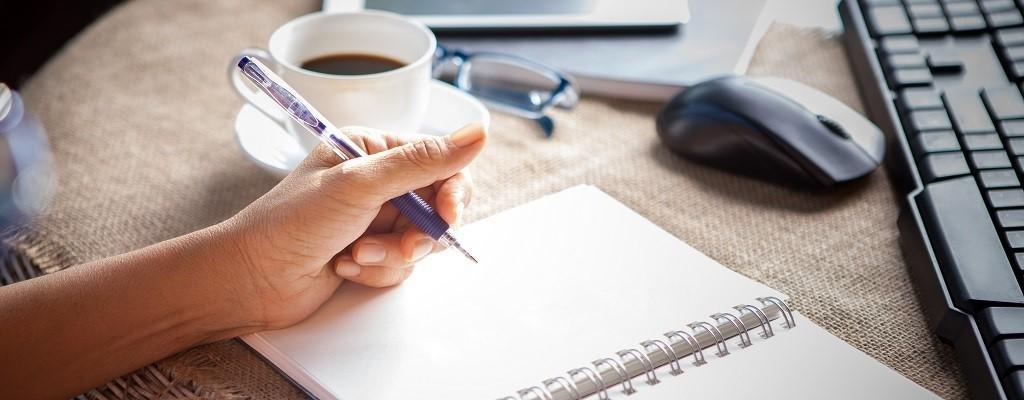 blank notepad on desk lady writing keyboard in background