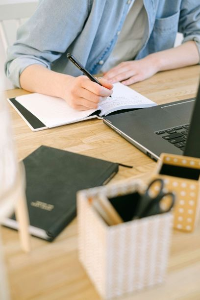 person writing in notebook on desk with computer